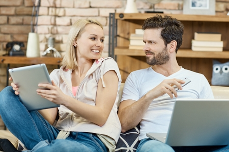 Young couple sitting on sofa, using tablet, mobile and laptop, smiling. Stock Photo