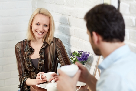 Beautiful young woman sitting at coffee table with boyfriend, smiling happy, looking at camera. photo