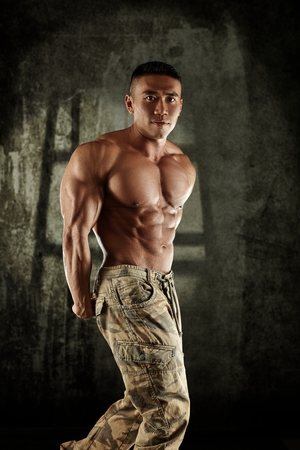 Male bodybuilder posing, stressing muscles with bare upper body.