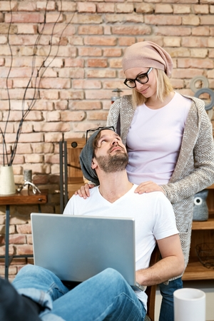 Young couple at home in cap and glasses, man sitting, using laptop computer, girlfriend standing behind, looking at each other.