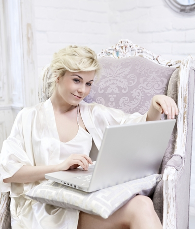 Smiling blonde woman sitting in baroque armchair, using laptop computer, wearing silk nightwear.