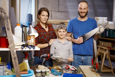 tinkering: Portrait of happy tinkering family in workshop, holding tinkering tools.