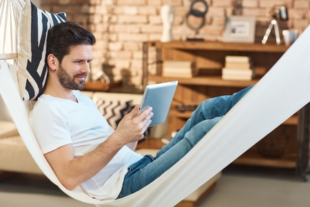 people relaxing: Man using tablet computer resting in hammock.