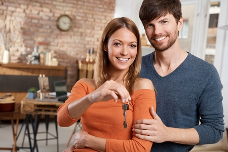 Young couple holding keys of new home, smiling happy. Stock Photo