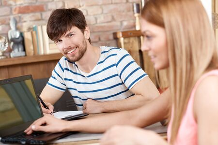 taking a wife: Happy young man sitting at desk at home with girlfriend. Stock Photo