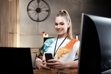 mobilephone: Young blonde girls sitting at desk, using mobilephone smiling.