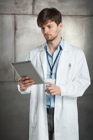 Giovane medico in piedi in camice da laboratorio, tenendo tablet computer.