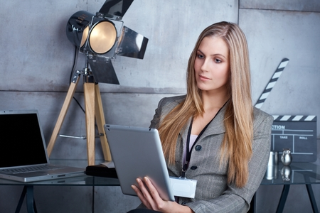 Young businesswoman sitting in studio, using tablet computer, working. photo
