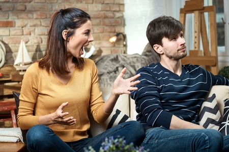 divorcing: Young couple arguing at home, woman shouting, man turning away head.