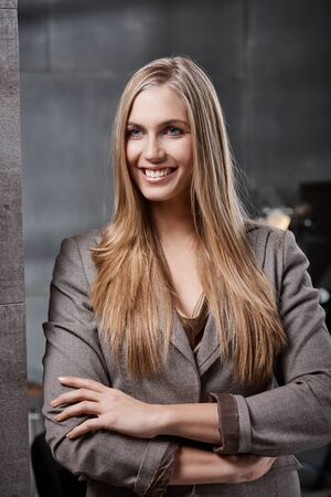 Portrait of happy young blonde businesswoman standing arms crossed, looking away. photo