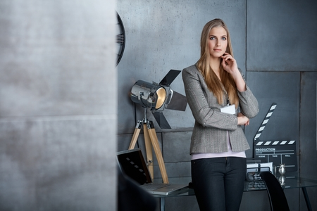 Young businesswoman standing in studio, looking at camera. photo