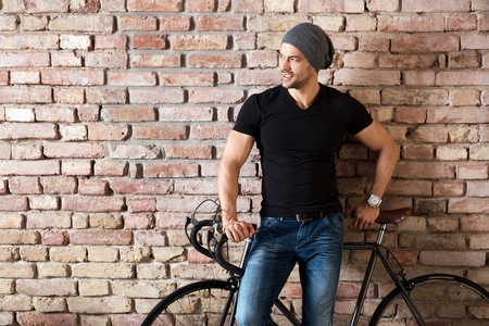 Portrait of a happy young athletic caucasian man with bicycle standing at brick wall, smiling.