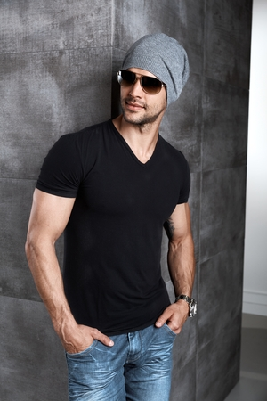 Portrait of trendy athletic young man in cap and sunglasses. Imagens