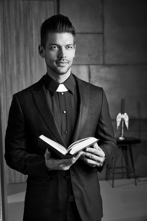 goodlooking: Portrait of good-looking young catholic priest holding book smiling.