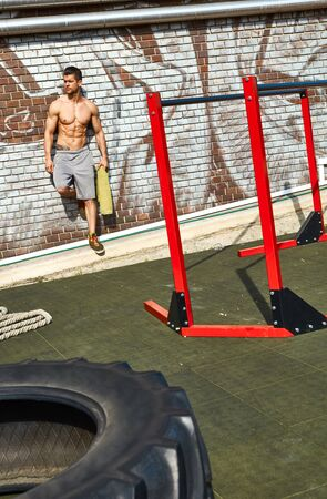 abdominal wall: Half-naked sporty man leaning against wall at outdoor gym.