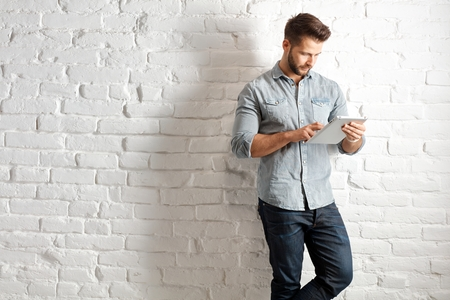 Young goodlooking caucasian man in casual clothes standing at white brick wall using handheld tablet, plenty of copyspace.