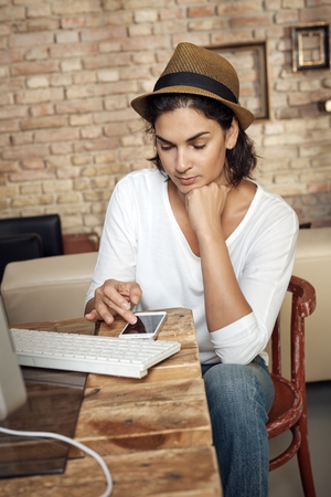 Trendy adult woman working at home using smartphone. Stock Photo