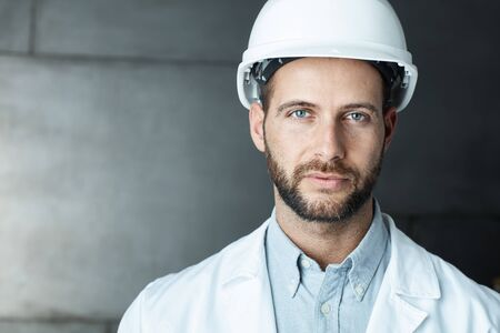 white coat: Portrait of confident young engineer wearing protective hardhat. Stock Photo