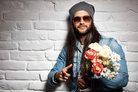 hair man: Portrait photo of rocker guy in sunglasses and woolly hat standing against brick wall holding bouquet of flowers for mothers day.