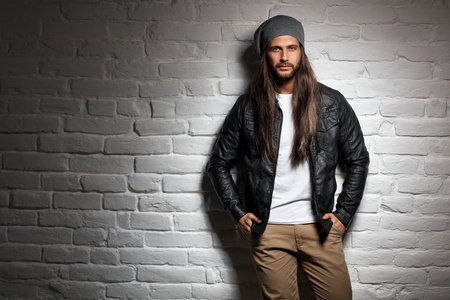 Man with long hair standing against wall, looking at camera. Copyspace.