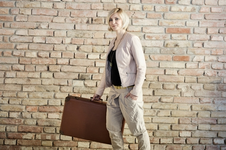 Young stylish woman walking, holding suitcase front of brick wall. photo
