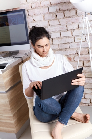 Female fashion blogger blogger posting to blog on laptop sitting at home.