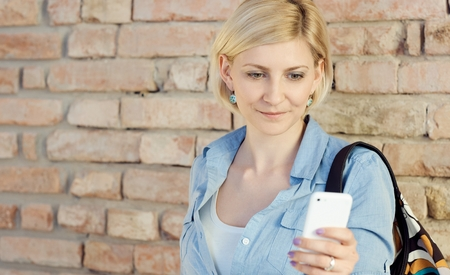 Young blonde woman using mobilephone, standing by brick wall. photo
