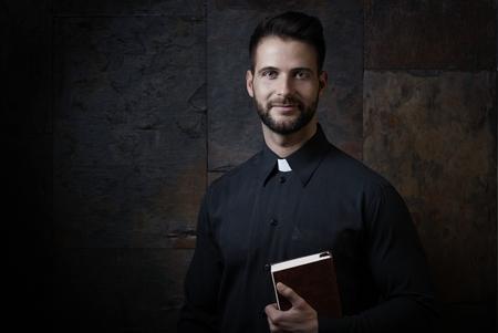 predicador: Retrato de sacerdote joven y guapo con el libro de oración contra el fondo oscuro.