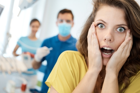 Female patient frightened from treatment at dentist's surgery. photo