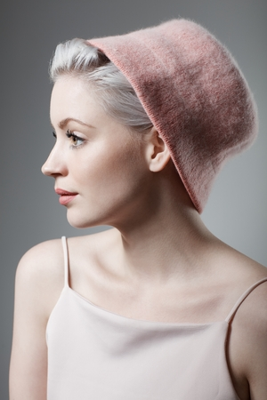 twiggy: Young woman in retro style wearing hat. Side view.