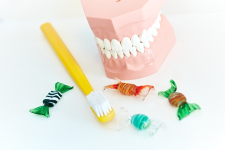 Closeup photo of plastic dental tooth model and toothbrush surrounded by sweets.