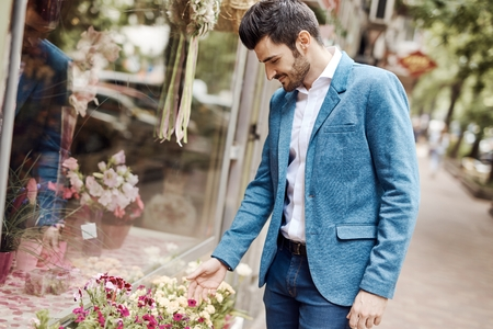 buying: Young man buying flowers outdoors. Stock Photo