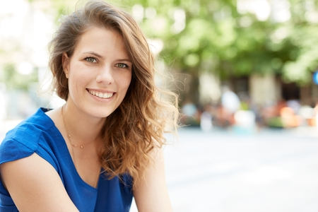 Outdoor portrait of attractive young woman smiling happy.