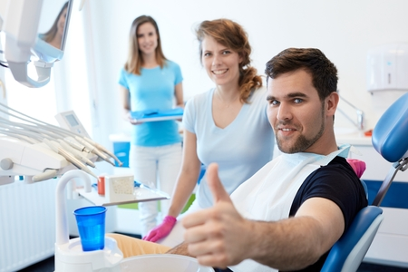 Confident young man after dental check-up, showing thumb-up. Stock Photo