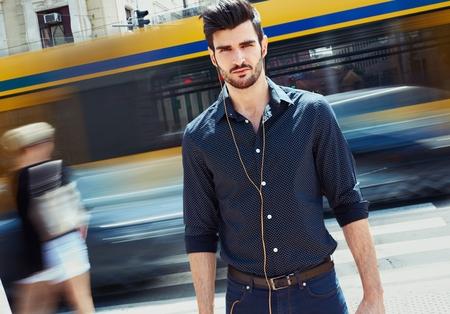 Foto all'aperto di bel giovane che cammina in città.