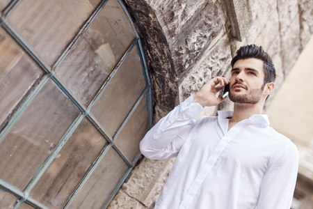 Outdoors portrait of handsome young man talking on mobilephone.