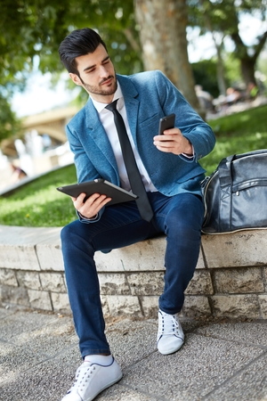 Young man sitting at park, using tablet and mobile.