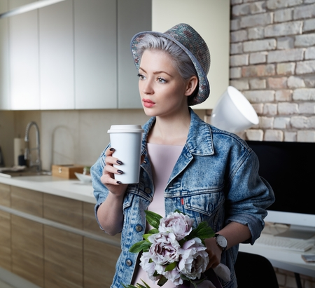 just arrived: Daydreaming young woman standing at home in kitchen, drinking coffee. Just arrived home. Stock Photo