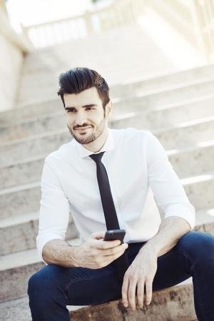 Ritratto all'aperto del giovane bello che sorride facendo uso del cellulare.