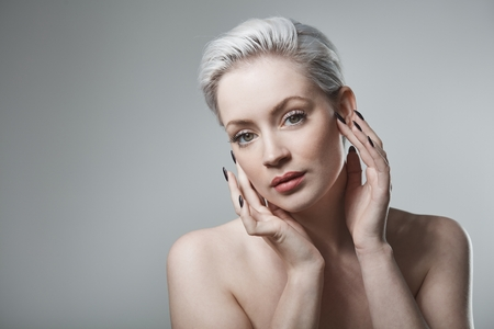 twiggy: Closeup portrait of beautiful young woman with short platinum blonde hair.