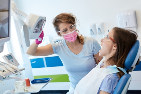 Female dentist treating patient in dentists office.