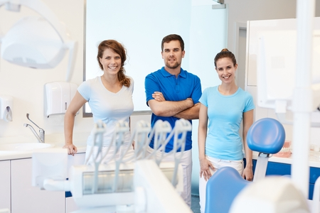 Portrait of confident dental surgeon and assistants in dentist's office. photo