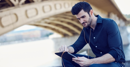 Young man using tablet computer outdoors.