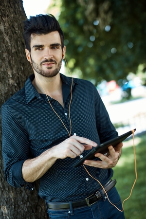 Daydreaming young man standing in park, using tablet computer.
