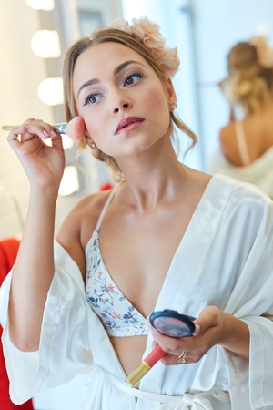 Beautiful young woman applying makeup in bathroom. Stock Photo