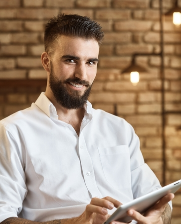 look latino: Happy bearded man using tablet at trendy home smiling, looking at camera.
