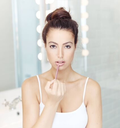 Portrait of attractive young woman applying lipstick. Stock Photo