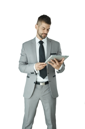 Portrait of adult businessman in suit using tablet isolated on white background.