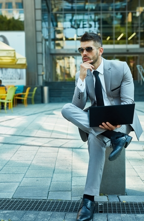man sit: Businessman seated outdoor if front of office building using laptop.