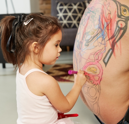 Little girl playing colouring her fathers back.